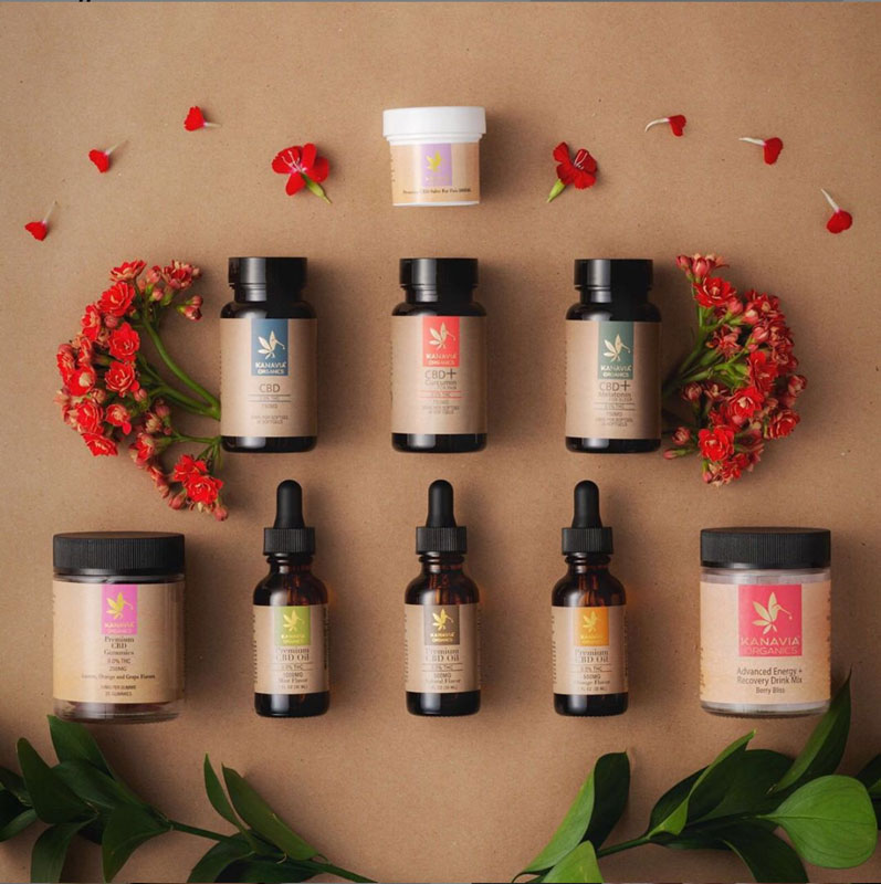 A selection of Kanavia's organic CBD products arranged near some flowers.