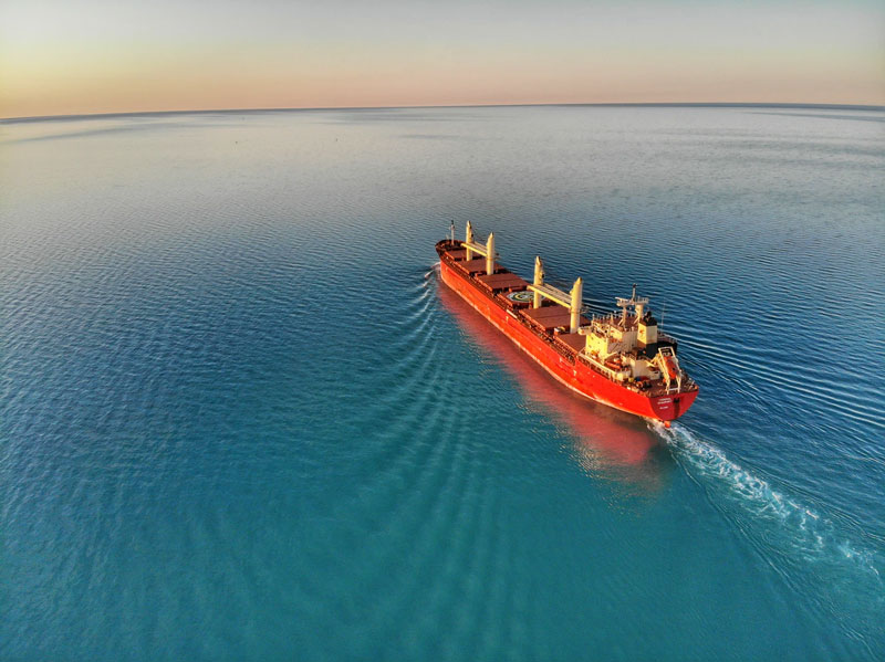 A red shipping carrier sails through bright blue water.