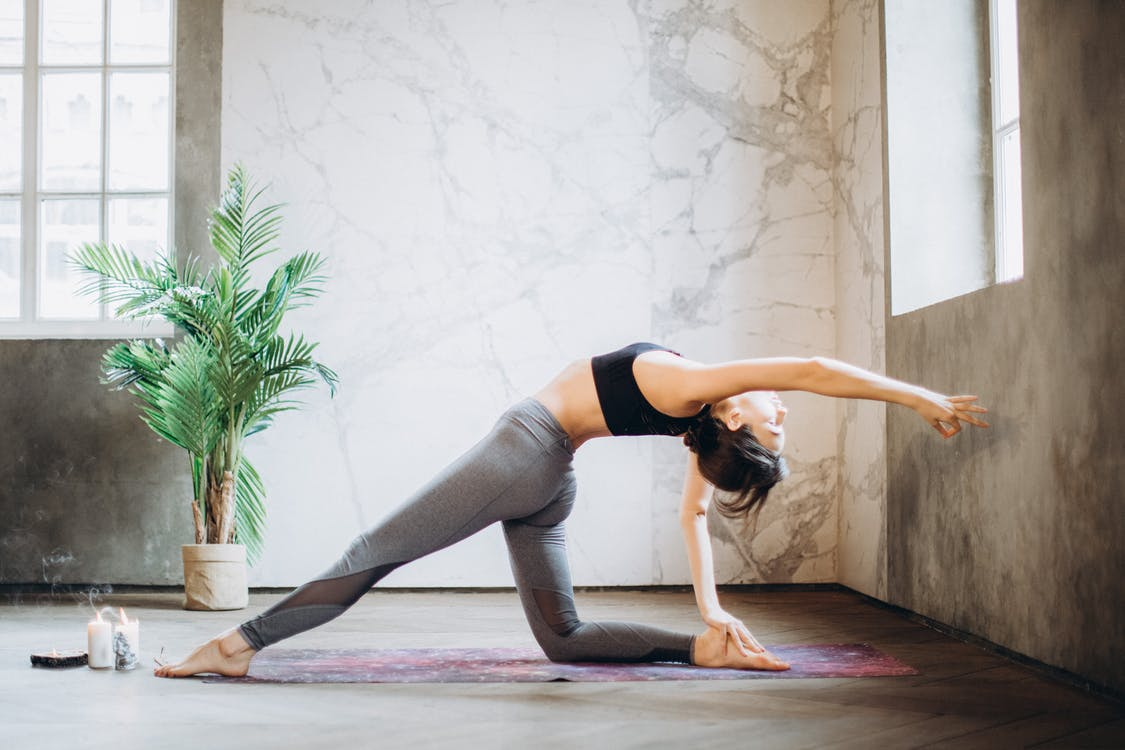woman in sports bra and leggings doing yoga on yoga mat