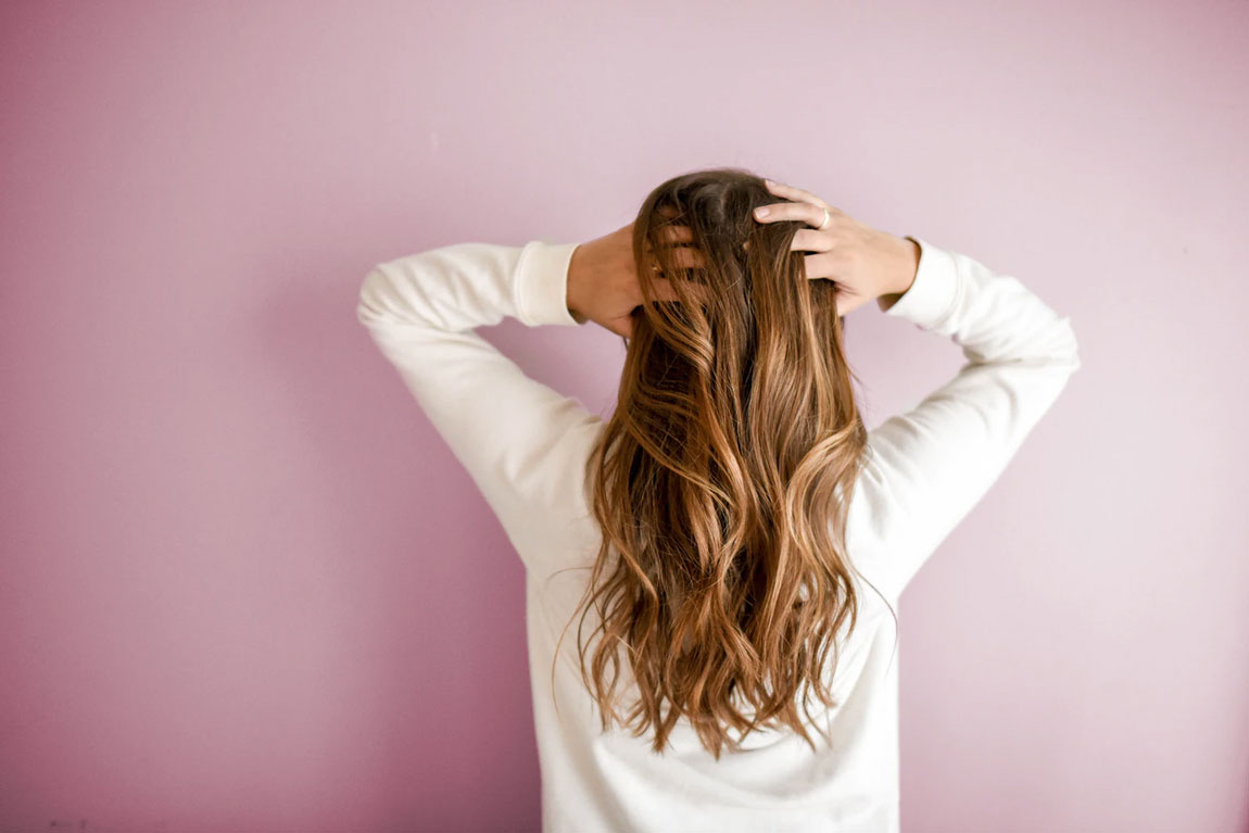 A woman stands and holds her head against a pink background.
